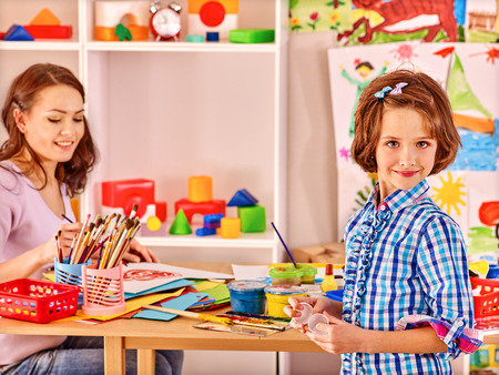kids class: Woman  with kid painting  in school. Education. Stock Photo