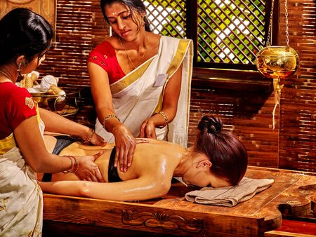 body oil: Young woman having oil Ayurveda spa treatment. Window background.