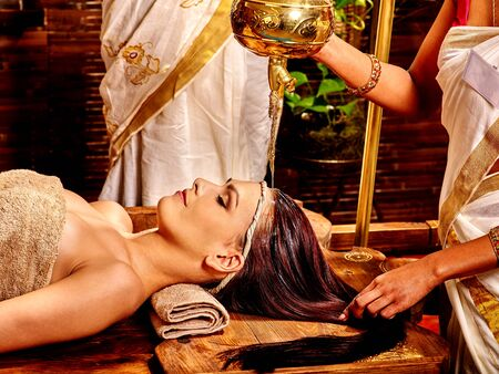 panchakarma: Young woman having oil Ayurveda spa treatment. Oil pouring from lamp.