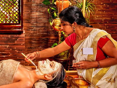 asian girl face: Indian woman does facial mask at ayurveda spa.