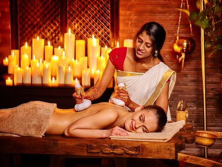 ayurvedic: White woman having ayurvedic massage with pouch of rice. A lot of burning candles.