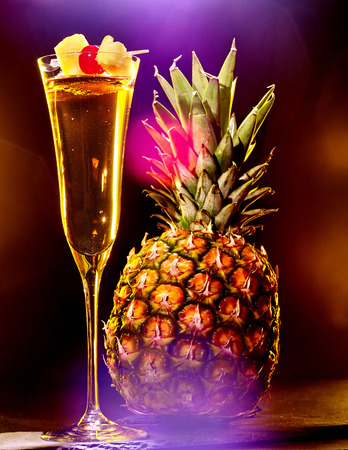 Champagne  cocktail with cherry skewer and whole pineapple with leaves . Cocktail card 42 photo