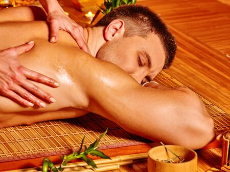 female therapist: Man getting massage in wooden bamboo spa. Female therapist. Stock Photo