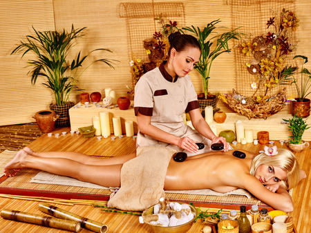 stone therapy: Woman getting stone therapy massage in bamboo spa. Two people.