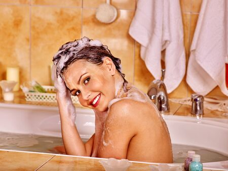 woman washing hair: Happy woman washing hair in bubble bath. A  lot of water. Stock Photo