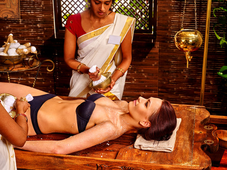 pouch: Woman having ayurvedic massage with pouch of rice. Indian girl.
