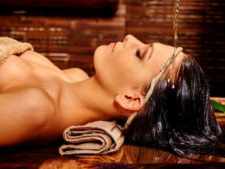 Junge Frau, die Ayurveda Spa-Behandlung. Gießen Öl. Standard-Bild