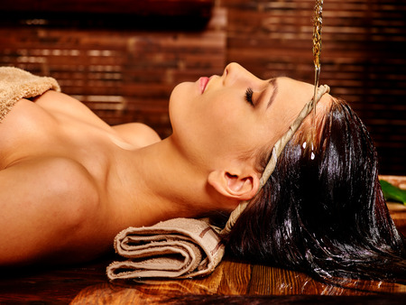 treatment: Young woman having Ayurveda spa treatment. Pouring oil. Stock Photo