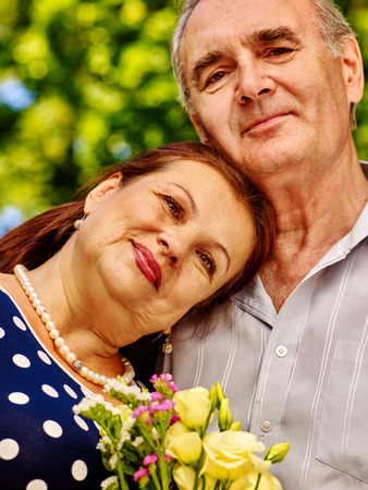 senior female: Happy old couple at summer  outdoor. Green tree on background. Stock Photo