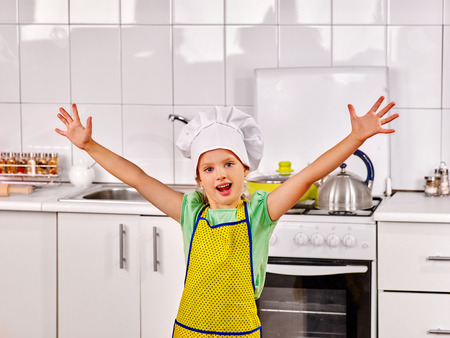 pinafore: Child wearing hat and apron cooking at kitchen. Hand up. Stock Photo