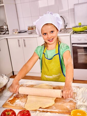 rollingpin: Smiling child female with rolling-pin dough at kitchen. Stock Photo