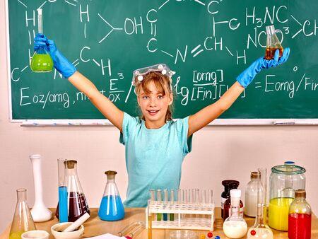 chemistry class: Child holding flask in chemistry class. Green blackboard background.