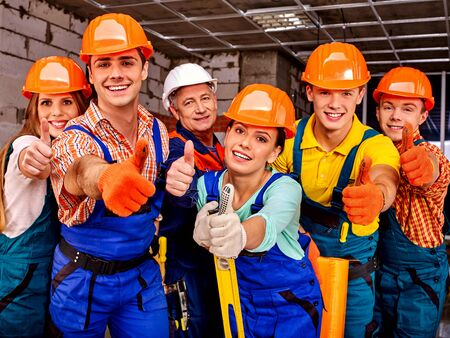 six persons: Group people in blue builder uniform thumb up. Six persons.