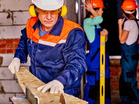 albañil: Viejo hombre en constructor azul con sierra circular.