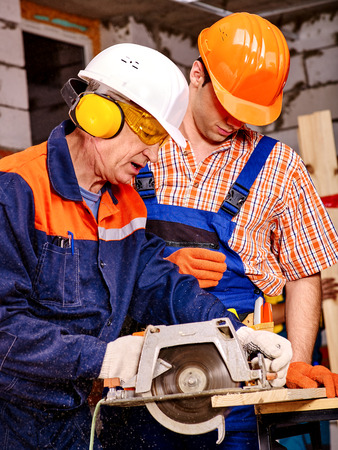 circular saw: Two men  builder with circular saw. Brick wall in the background