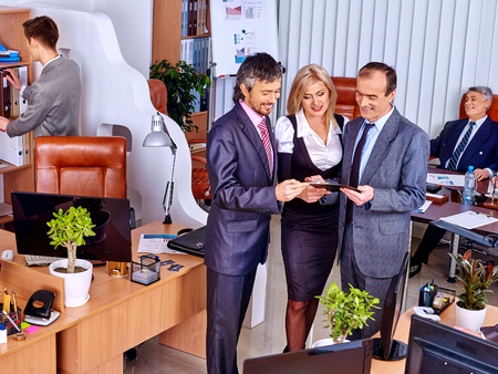 three persons: Happy group business people together  in office. Three persons standing. Stock Photo