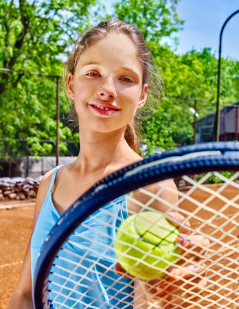 teener: Girl sportsman with racket and ball on  tennis court. Green tree ang blue sky on background. Stock Photo