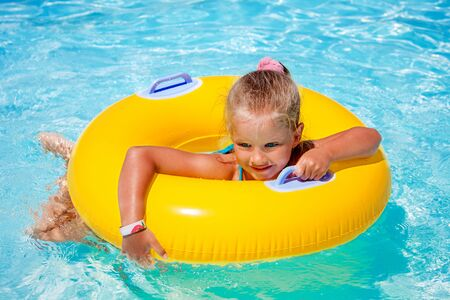 float tube: Child female on inflatable yellow ring in swimming pool. Stock Photo