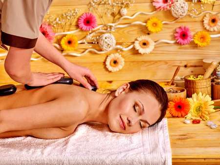 Happy woman getting stone therapy massage in spa. Herbera flower on wooden wall. Stock Photo