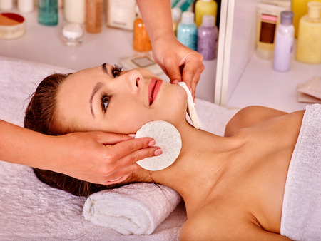 masajes faciales: Joven mujer recibiendo masaje facial en el spa de belleza. Toalla debajo del cuello.
