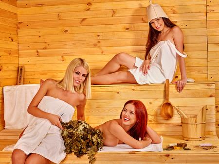 bathroom women: Group women sitting on bench in sauna.