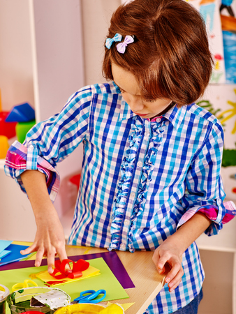 playschool: Little girl painting bow on picture  in school. Education. Stock Photo