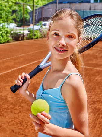 Teenager girl athlete with racket and ball on  brown tennis court.