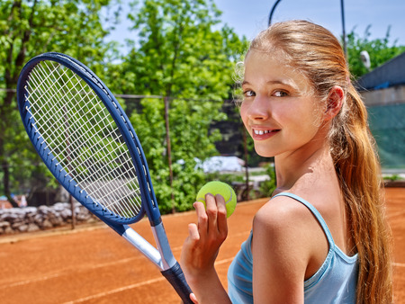 teener: Girl sportsman with racket and ball on  tennis court. Green tree ang blue sky on background. Looks over her shoulder