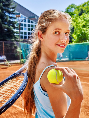 Girl sportsman with racket and ball on  tennis court. Green tree ang blue sky on background. Looks over her shoulder. Stadion on background.