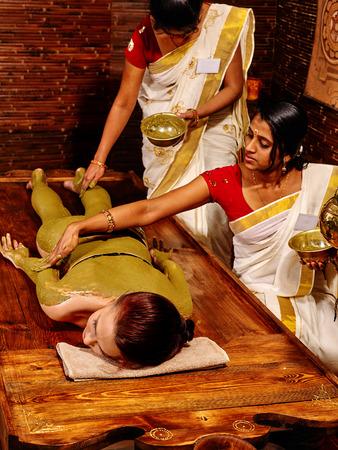 panchakarma: Young woman having body Ayurveda spa massage. Two indian women. Stock Photo