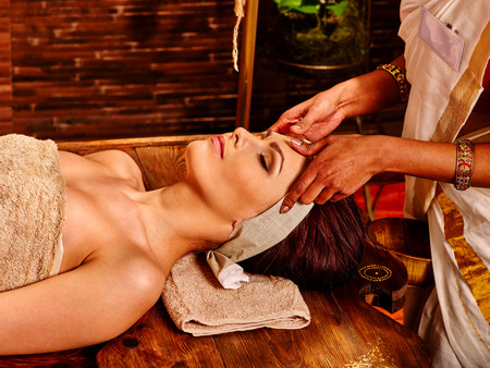 Woman having facial  ayurveda spa treatment. Wooden brown bed Stock Photo