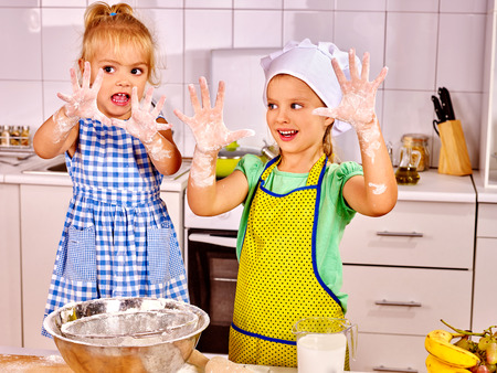 messy kids: Child with rolling-pin dough at kitchen. Messy kids Stock Photo