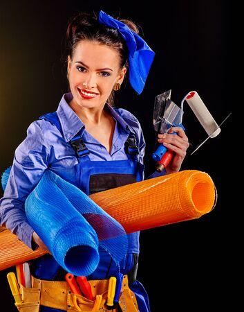 outils construction: Femme heureuse constructeur avec des outils de construction sur fond noir.