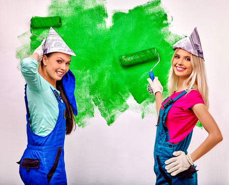 painter girl: Happy girlfriend paint wall at home. Stock Photo