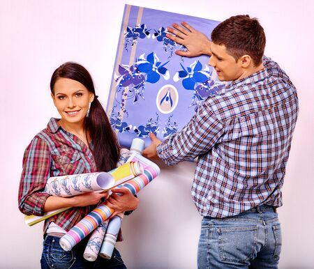gluing: Happy husband and wife gluing wallpaper at home. Stock Photo