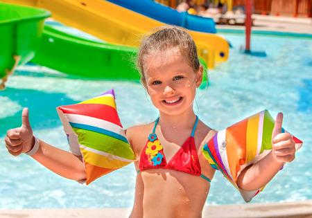 armbands: Child with colored armbands playing in swimming pool. Summer outdoor.
