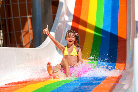 child in bikini: Happy child girl in yellow bikini sliding water park and show thumb up.