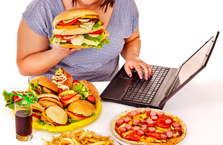 high calorie foods: Body part of woman eating fast food at work. Isolated.