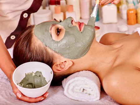 beauty spa: Woman with green clay facial mask in beauty spa.