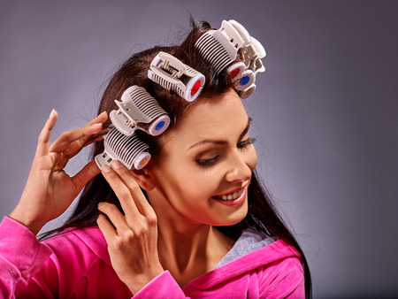 hot rollers: Happy woman wear hair curlers on head. Gray background.
