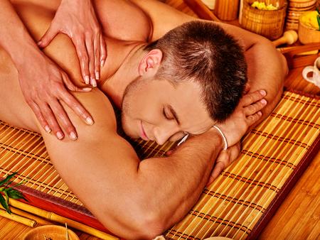massage huile: Bel homme se massage au bambou spa. Thérapeute.