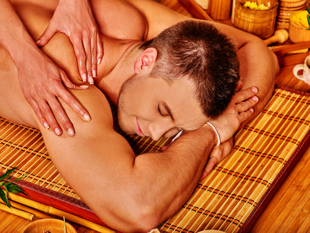 Handsome man getting massage in bamboo spa. Female therapist.
