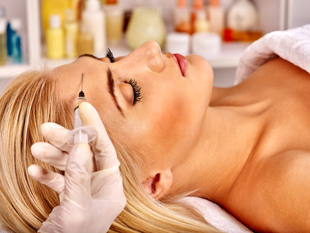botox: Beauty woman giving botox injections on forehead.
