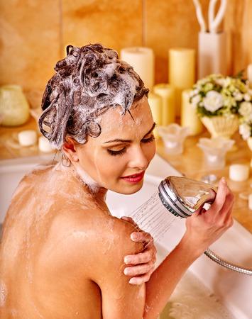 mujer bañandose: La mujer lava su cabeza al baño casa. Verter el agua.