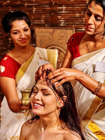 panchakarma: Young woman having head ayurveda spa treatment. Two masseuses. Stock Photo