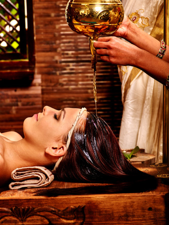 panchakarma: Young woman having oil Ayurveda spa treatment. Massage oil poured on forehead.