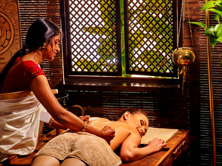panchakarma: Young woman having oil Ayurveda spa treatment. Window background.