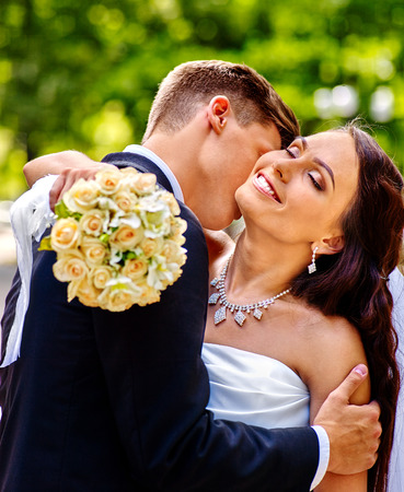 gently: Groom kissing bride outdoor. Man gently embraces girl. Green background.