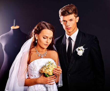Happy couple try wedding dress in shop. Black background. photo