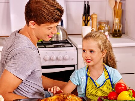 daugther: Young man cooking chicken with daugther at kitchen. Stock Photo
